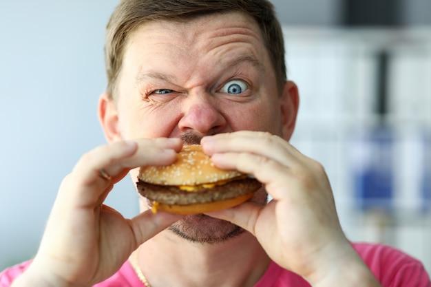 Grappige bebaarde man met idioot gelaatsuitdrukking eten grote hamburger
