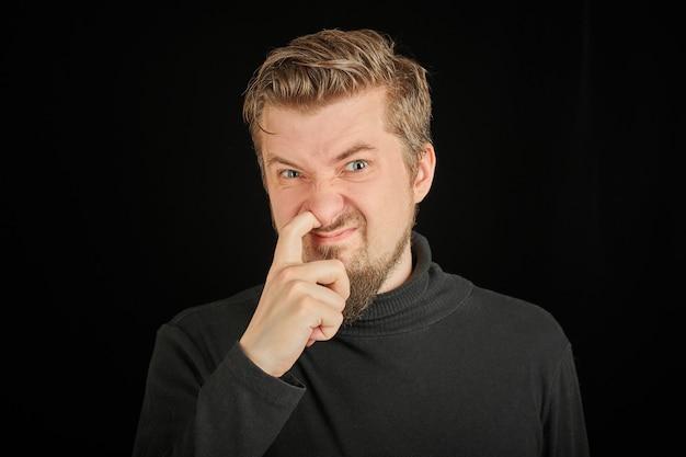 Grappige bebaarde man zijn neus plukken, zwarte achtergrond. jonge kerel in zwarte polohals trui. domme, domme man.