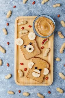 Grappige beer en aap gezicht sandwich met pindakaas, banaan en zwarte bessen, pinda's, bovenaanzicht
