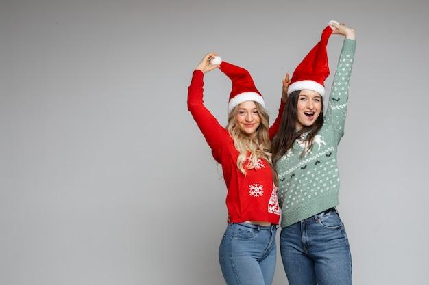 Grappige beste vrienden die kerstmutsen omhoog trekken.