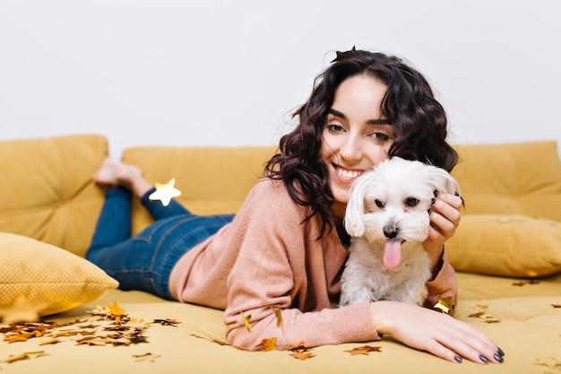 Grappige binnenlandse momenten van gelukkige jonge vrouw die op bank thuis met binnenlands huisdier koelen. plezier hebben, gouden tinsels, glimlachen, opgewekte stemming, geweldige, echte positieve emoties