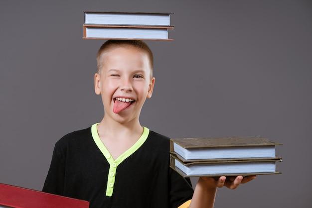 Grappige blanke jongen met boeken in zijn handen en op zijn hoofd toont haar tong op een grijze muur in vrijetijdskleding terug naar schoolconcept