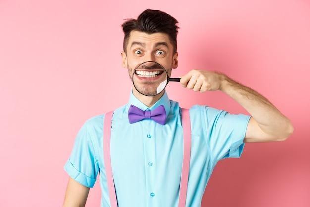 Grappige blanke man in vlinderdas met zijn witte glimlach tanden met vergrootglas, vrolijk kijken naar camera, staande op roze achtergrond.