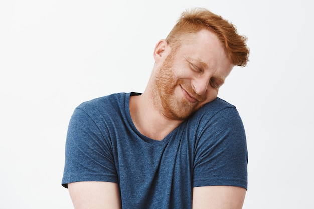 Grappige blanke roodharige man met borstelharen, kantelend hoofd en leunend op schouder met mooie en schattige uitdrukking, glimlachend met gesloten ogen, teder en meisjesachtig over grijze muur