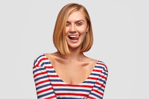 Grappige blanke vriendin heeft vreugde, glimlacht breed, toont tong, heeft afgeknipt kapsel