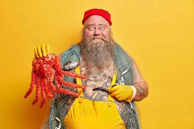 Grappige blauwogige zeeman houdt grote octopus en rookpijp vast, leidt het leven op zee, gekleed in zeemanskleding