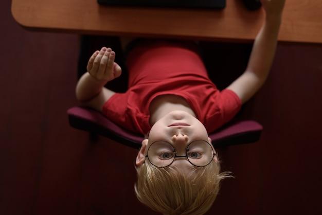 Grappige blonde jongen in glazen die bij laptop rusten. internet en kleuter.
