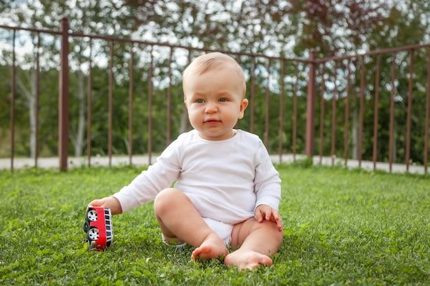 Grappige blonde schattige baby zittend in het gras en spelen met speelgoed auto