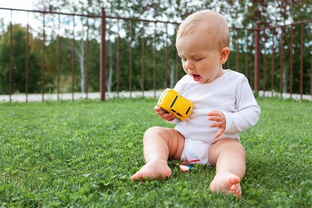 Grappige blonde schattige kleine blauwogige baby in witte romper zitten in groen gras en spelen met gele auto speelgoed, kopie ruimte, horizontaal