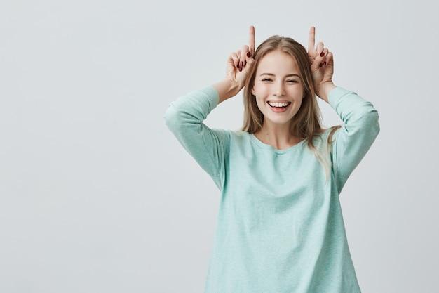 Grappige blonde vrouw die breed houdend vingers boven hoofd glimlacht. hoorns gebaar