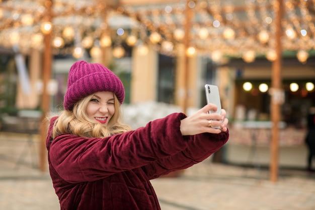 Grappige blonde vrouw die plezier heeft en zelfportret maakt op de achtergrond van de slinger in kiev
