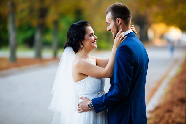 Grappige bruid hartstochtelijk kijken naar elkaar op het spoor in de tuin