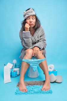 Grappige brunette aziatische vrouw maakt grimas kruist ogen draagt badjas slaapmasker slipje naar beneden getrokken heeft slaperige uitdrukking poses in toilet met noodzakelijke items rond geïsoleerd over blauwe muur