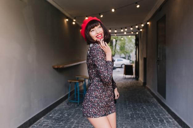 Grappige brunette meisje in trendy franse rode baret speels poseren met schattige glimlach, haar kin aan te raken. schattige jonge donkerharige vrouw in korte vintage jurk met plezier na het werk en lachen