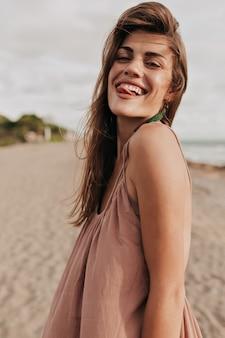 Grappige charmante dame met bruin haar maakt gezichten en heeft plezier op het strand in zonlicht