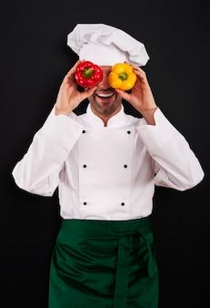 Grappige chef-kok die zijn ogen van paprika behandelt