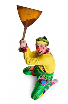 Grappige clown met een balalaika die op een wit wordt geïsoleerd