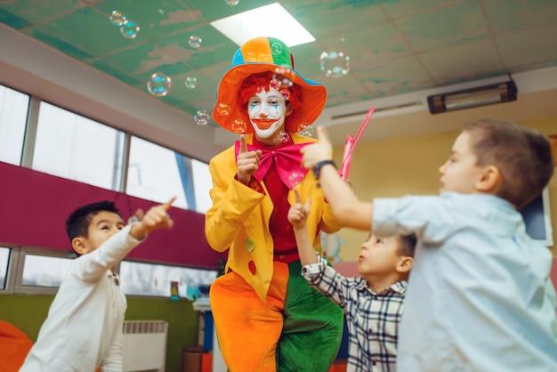 Grappige clown met kinderen blaast zeepbellen op