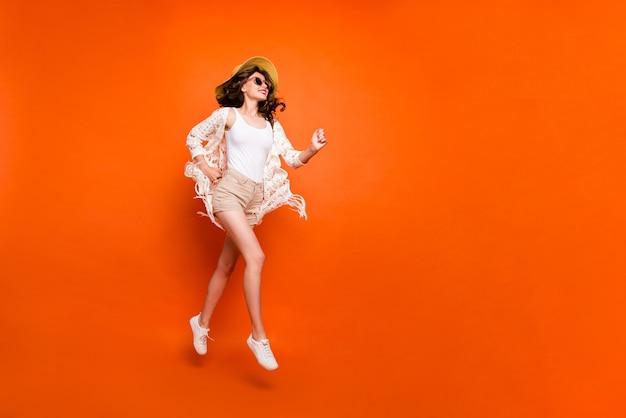 Grappige dame hoog springen, wandelen, stijlvolle zonnehoed dragen vintage stijlvolle trendy cape shorts.