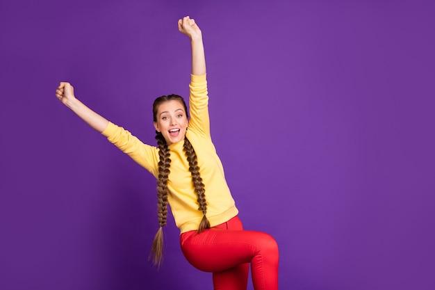 Grappige dame lange vlechten handen opsteken vieren beste winnen geweldige dag dragen casual gele trui rode broek geïsoleerde paarse kleur muur