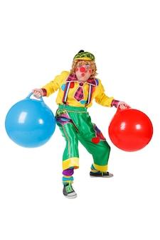 Grappige die clown met ballen in studio op witte achtergrond wordt geïsoleerd