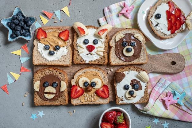 Grappige dierengezichten toast met smeersels, banaan, aardbei en bosbes