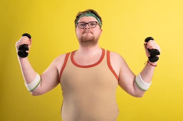 Grappige dikke man doet oefeningen met halters. overgewicht. gele achtergrond.