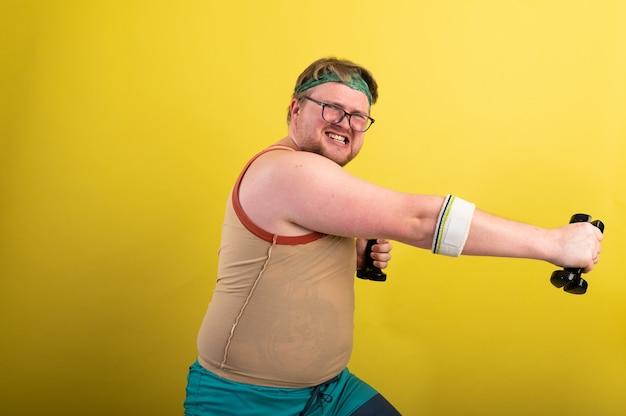 Grappige dikke man doet oefeningen met halters overgewicht gele achtergrond