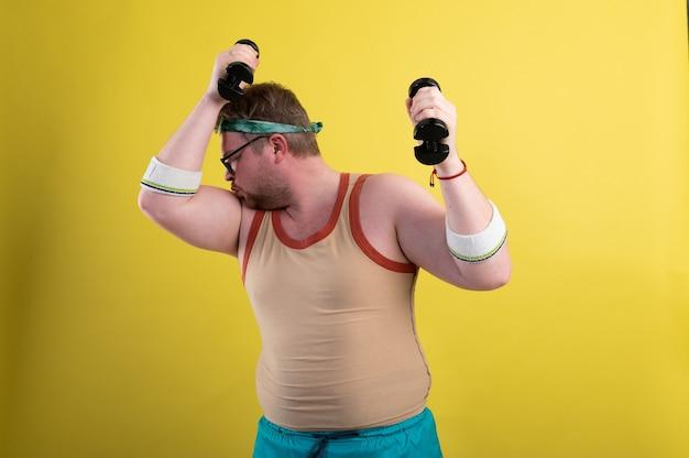 Grappige dikke man gaat sporten doet een halter biceps oefening k-beeldmateriaal van hoge kwaliteit
