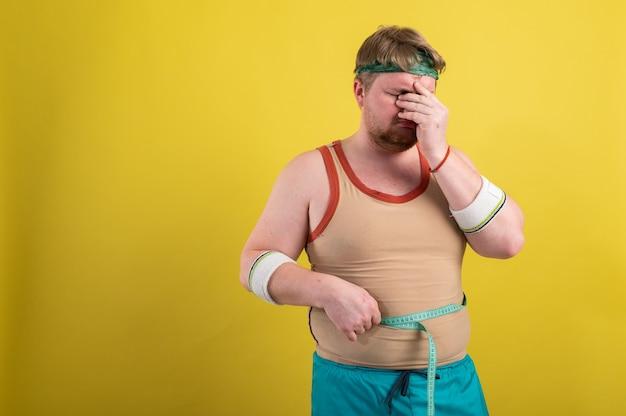 Grappige dikke man in sportkleding neemt metingen van lichaamsvolume.