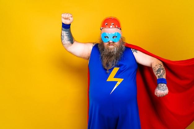 Grappige dikke man met superheldenkostuum die als bovenmenselijk fungeert met portret van speciale krachten op gekleurde muur