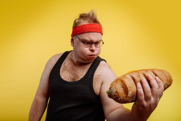 Grappige dikke man zweet tijdens het tillen van hamburger