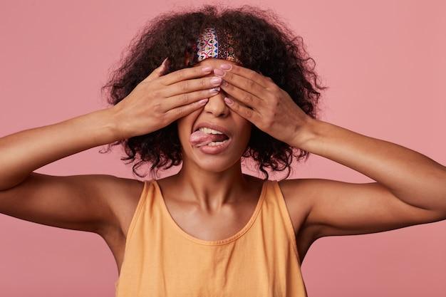 Grappige donkere huid krullend brunette vrouw met kort kapsel haar ogen met handen sluiten en haar tong tonen, poseren in vrijetijdskleding
