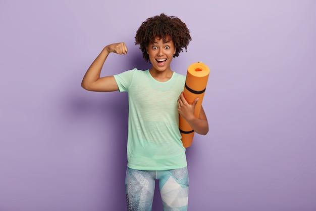 Grappige donkere vrouw heft arm op, toont spieren na training, houdt karemat vast, traint regelmatig in de sportschool met coach, gekleed in sportkleding, geïsoleerd op paarse muur. kracht concept