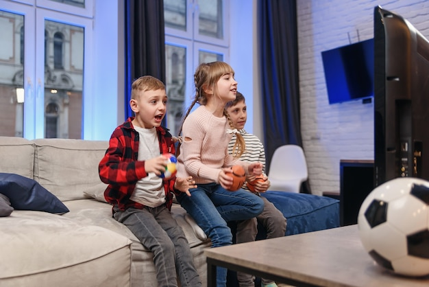 Grappige drie kindvrienden zitten thuis op de bank en genieten van voetbalwedstrijd