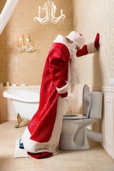Grappige dronken kerstman in rood kostuum plassen in het toilet. alcoholische kerstman