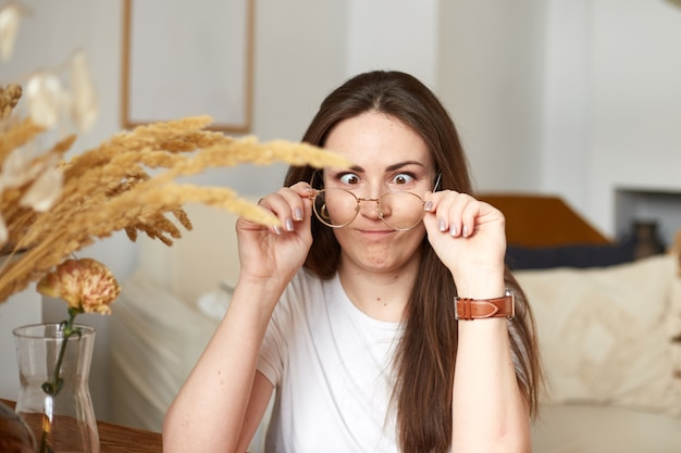 Grappige duizendjarige vrouw met een bril in de keuken van de ecostijl. trendy kleuren. natuurlijk licht
