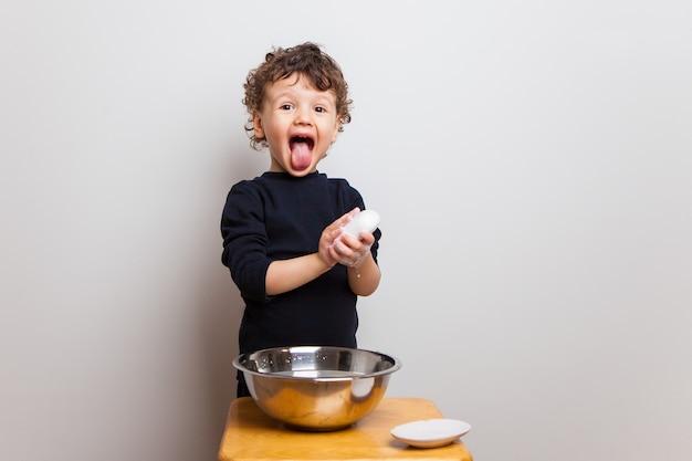 Grappige emotionele baby dabbelt, wast zijn handen met zeep en toont tong.
