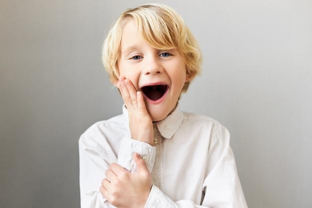 Grappige emotionele europese jongen die echte oprechte reactie uitdrukt, de mond wijd open houdt en de wangen aanraakt, opgewonden is door iets, schreeuwt wow. verrassing en verbazing