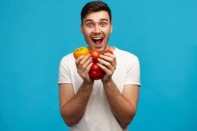Grappige emotionele jonge man in wit overhemd paprika en tomaten in beide handen houden, opgewonden blik hebben, mond wijd openen, dolblij met verse biologische groenten uit zijn tuin
