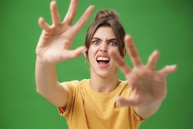 Grappige emotionele vrouw die pretgezicht maakt die handen naar voren trekt om aan te vallen of iets te grijpen