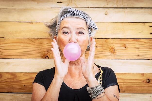 Grappige en alternatieve oude mensen kaukasische mooie vrouw met roze bubble kauwgom - portret van jeugd actieve senior dame plezier - geen limiet leeftijd levensstijl concept