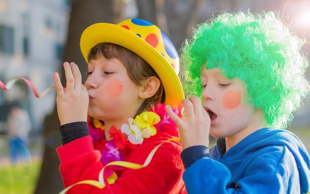 Grappige en carnaval-jonge geitjes die openlucht glimlachen spelen