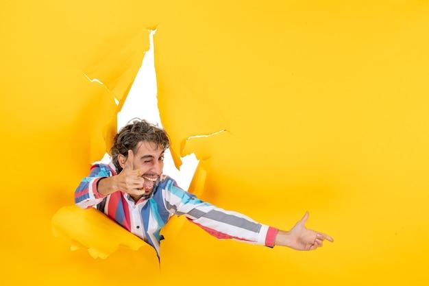 Grappige en emotionele jongeman poseert in een gescheurde gele achtergrond van een papieren gat, wijst iets en maakt een goed gebaar