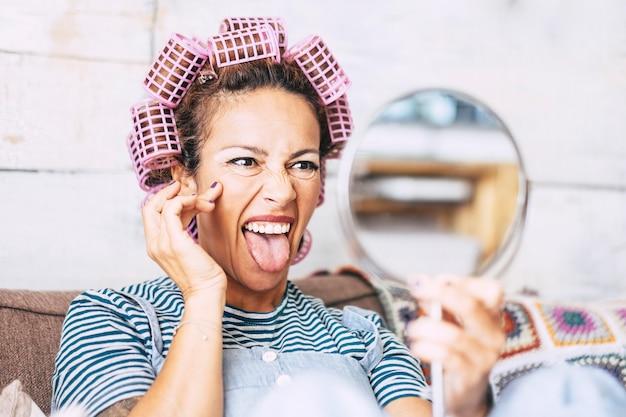 Grappige en gekke volwassen mooie aantrekkelijke vrouw die uitdrukkingen in de spiegel doet en zich klaarmaakt met krulspelden en make-up - thuis schoonheidsverzorging mensen concept met leeftijdsrimpels