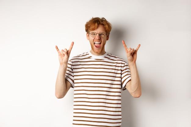 Grappige en gelukkige roodharige man met plezier, rock-n-roll hoorn en steekt tong tonen, genieten van feest, staande op witte achtergrond