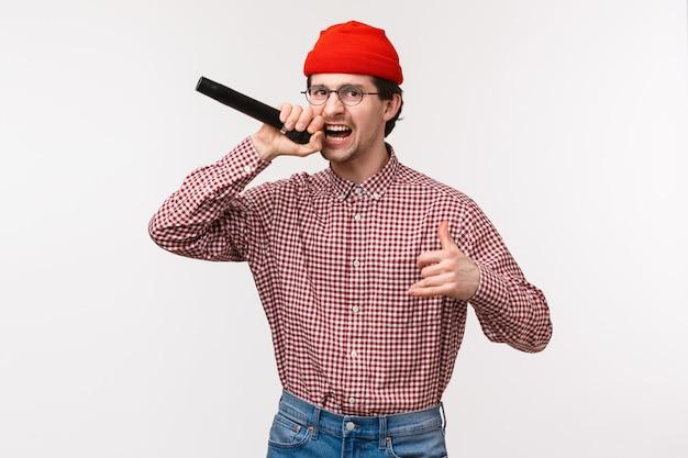 Grappige en gepassioneerde coole hipster-man in rode muts en bril die raplied zingen, opgewonden acteren, microfoon vasthouden, plezier hebben in karaoke met vrienden, staande witte muur vrolijk