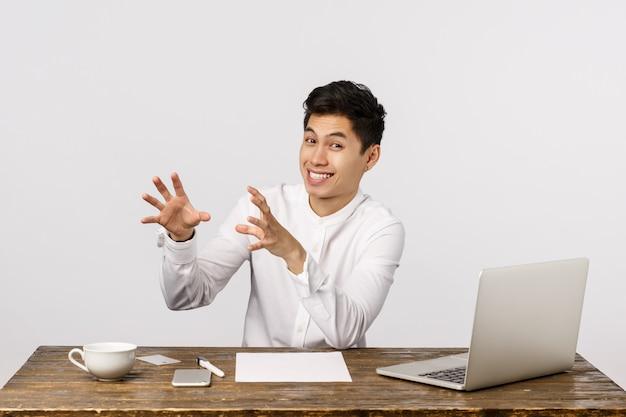 Grappige en knappe chinese man in wit overhemd, iets vangen als zittend bureau, spelen met collega's tijdens werkuren, vrolijk glimlachen, gek rond