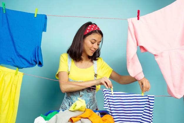 Grappige en mooie huisvrouw die huishoudelijk werk doet dat op blauwe ruimte wordt geïsoleerd