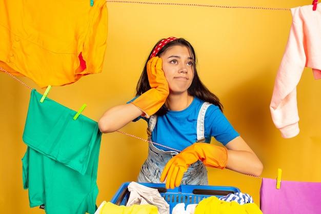 Grappige en mooie huisvrouw die huishoudelijk werk doet dat op gele achtergrond wordt geïsoleerd. jonge blanke vrouw omringd door gewassen kleren. huiselijk leven, heldere kunstwerken, huishoudelijk concept. dromerig.